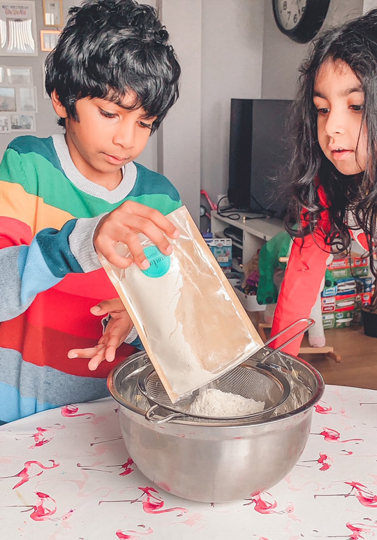 Children pouring biscuit mix into sieve