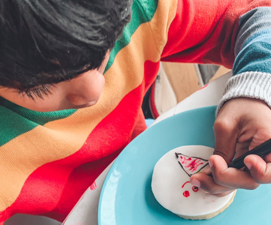 Boy decorating icing with cake pen