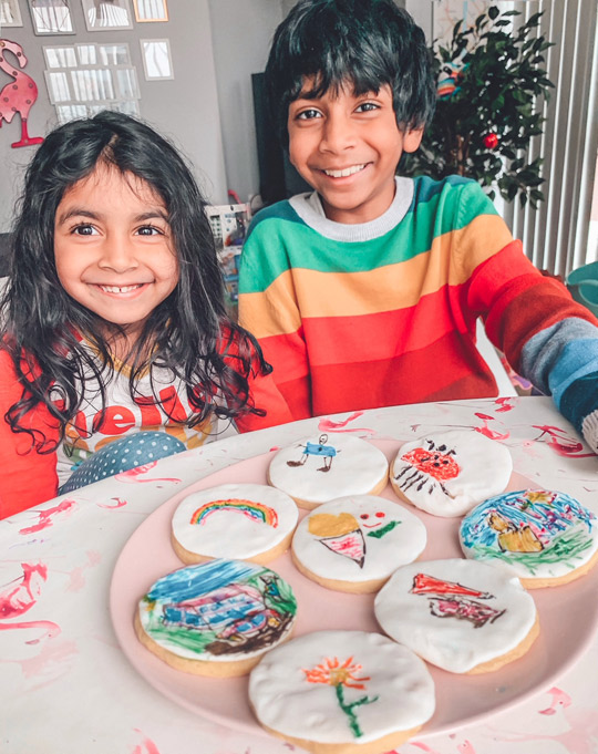 Photo of two smiling children with their decorated biscuits