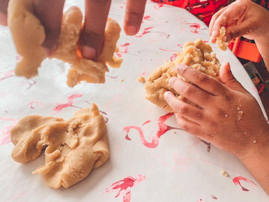 Children kneading biscuit dough